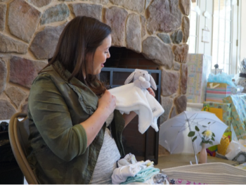 woman opening gifts at a baby shower