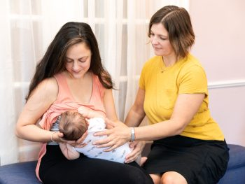 lactation-consultant-working-with-a-new-mom-and-newborn