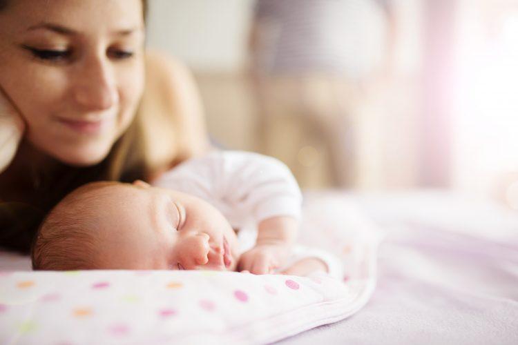 Mom gazing at sleeping newborn
