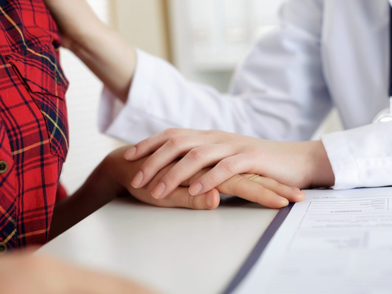 Close up view of female doctor touching patient hand for encouragement