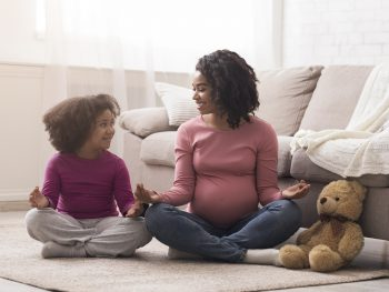 Pregnant-black-mother-and-her-little-daughter-practicing-yoga-at-home