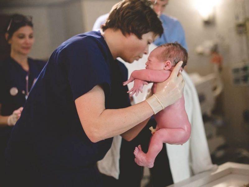 midwife holding newborn baby