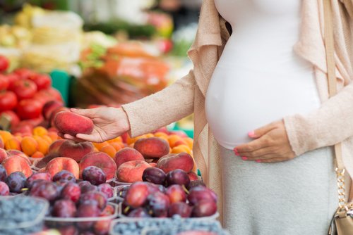 pregnant woman shopping for fruit