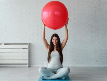 pregnant-woman-lifting-exercise-ball-over-her-head