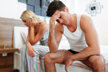 frustrated couple siting on bed