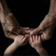 child's hands holding older person's hands